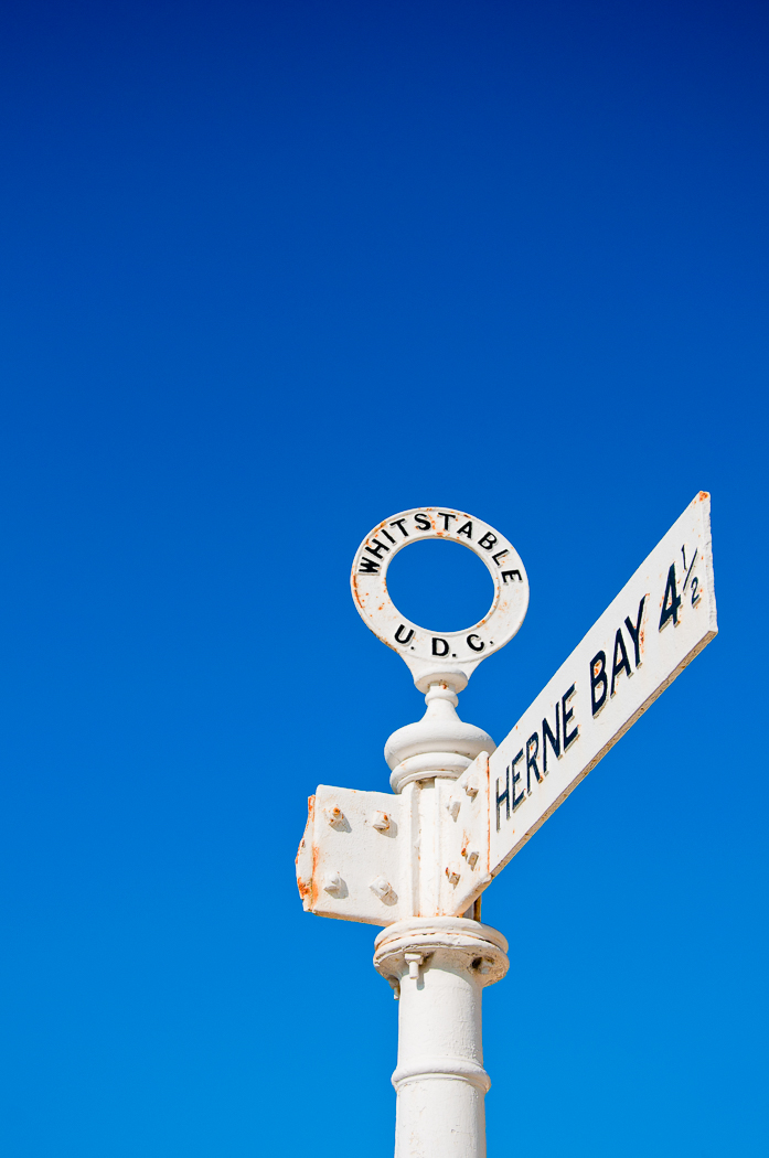 A damaged Whitstable signpost against a clear blue sky.